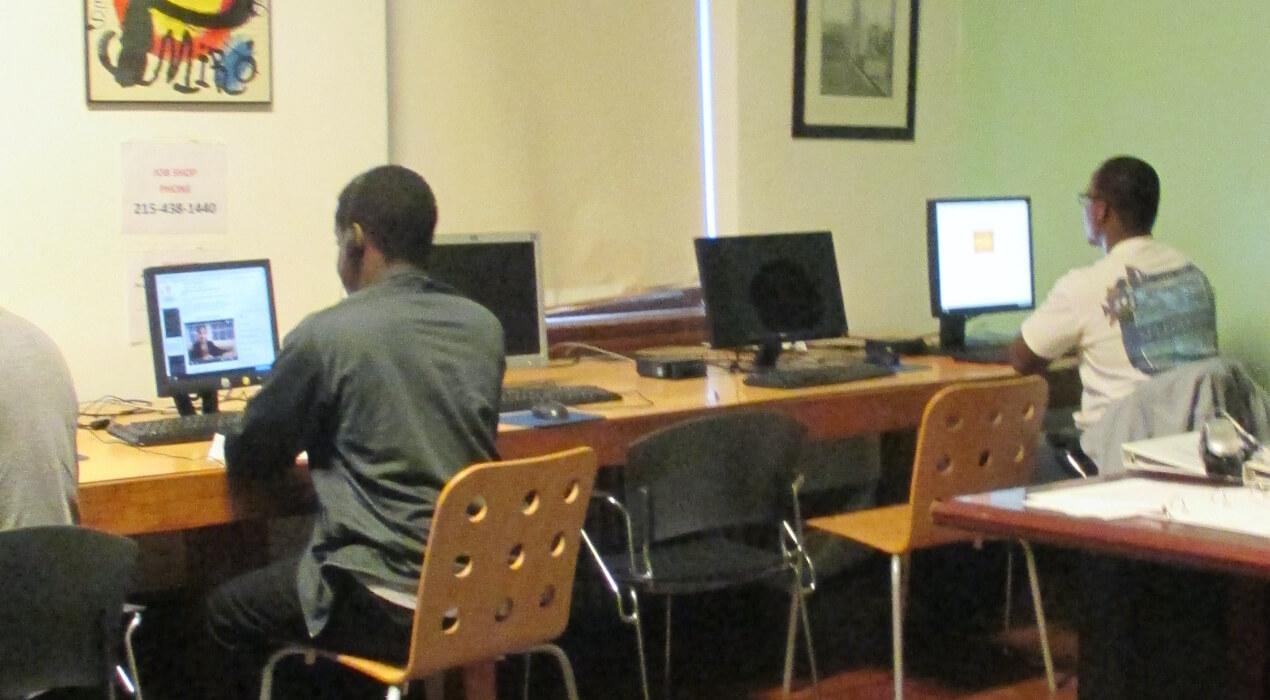 Men sitting at a computer desk
