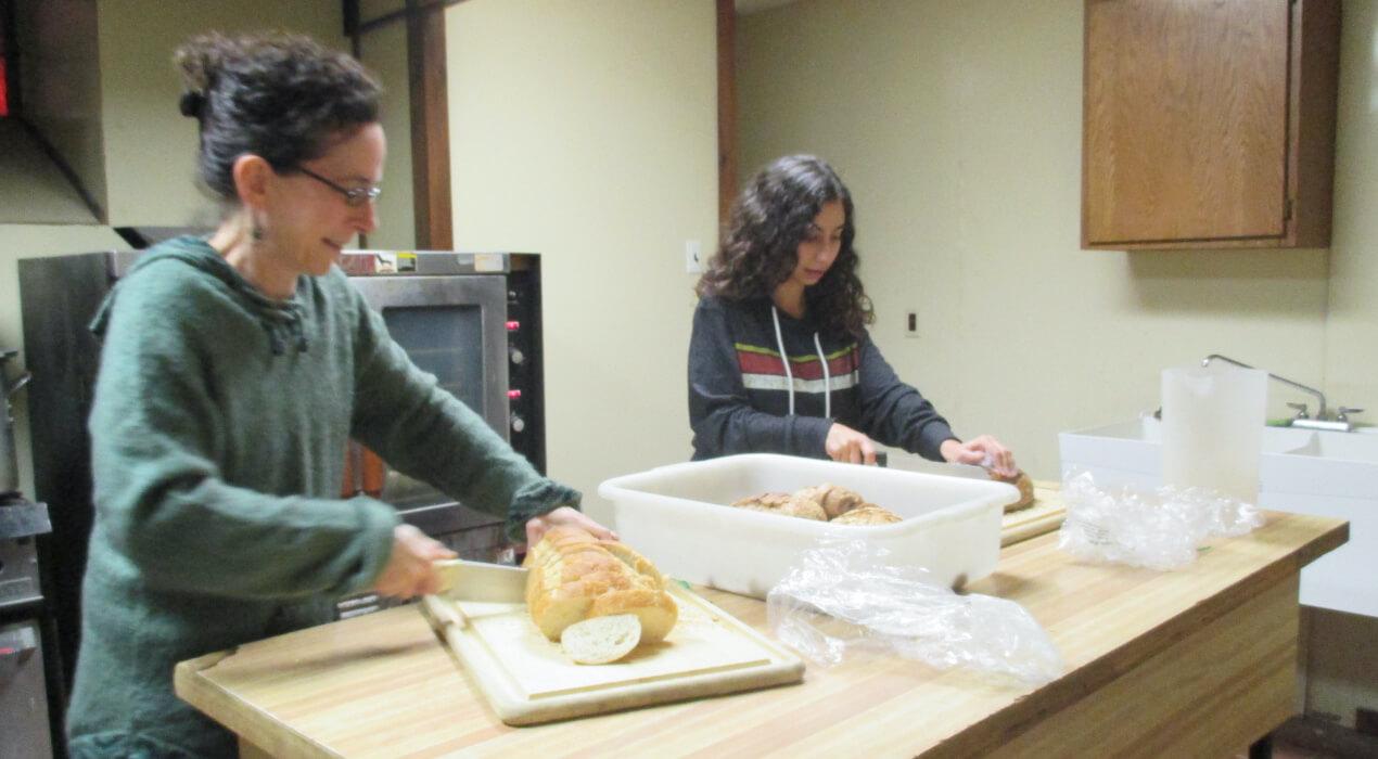 Two women cutting bread
