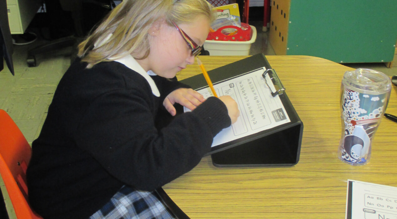 Child practicing her writing at a desk
