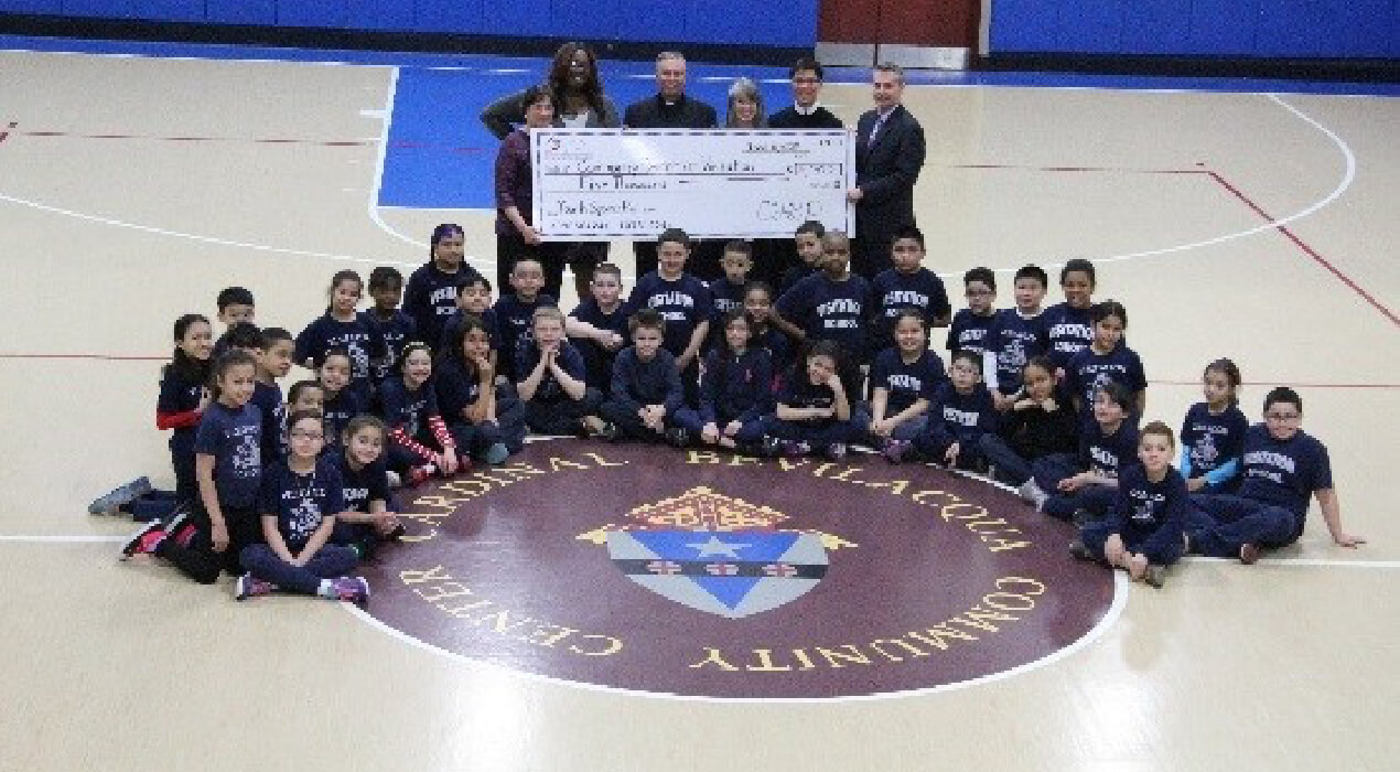 Community Center at Visitation receiving their grant in the gym